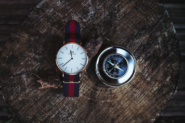 round silver colored analog watch next to compass